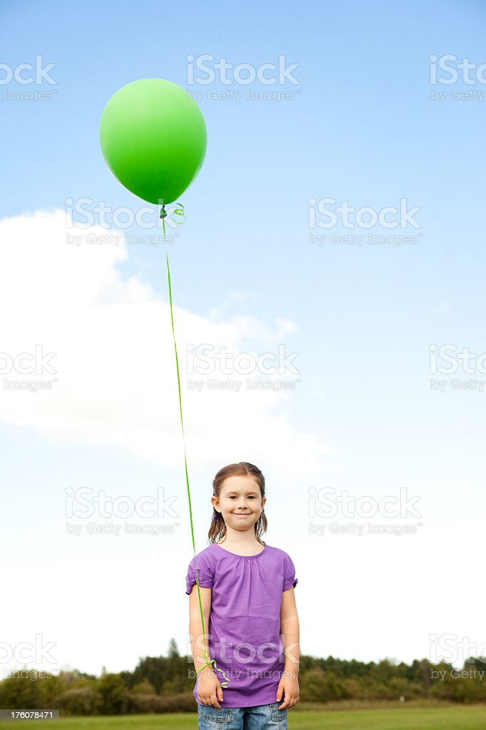 Happy Little Girl Holding a Balloon Outside royalty-free stock photo