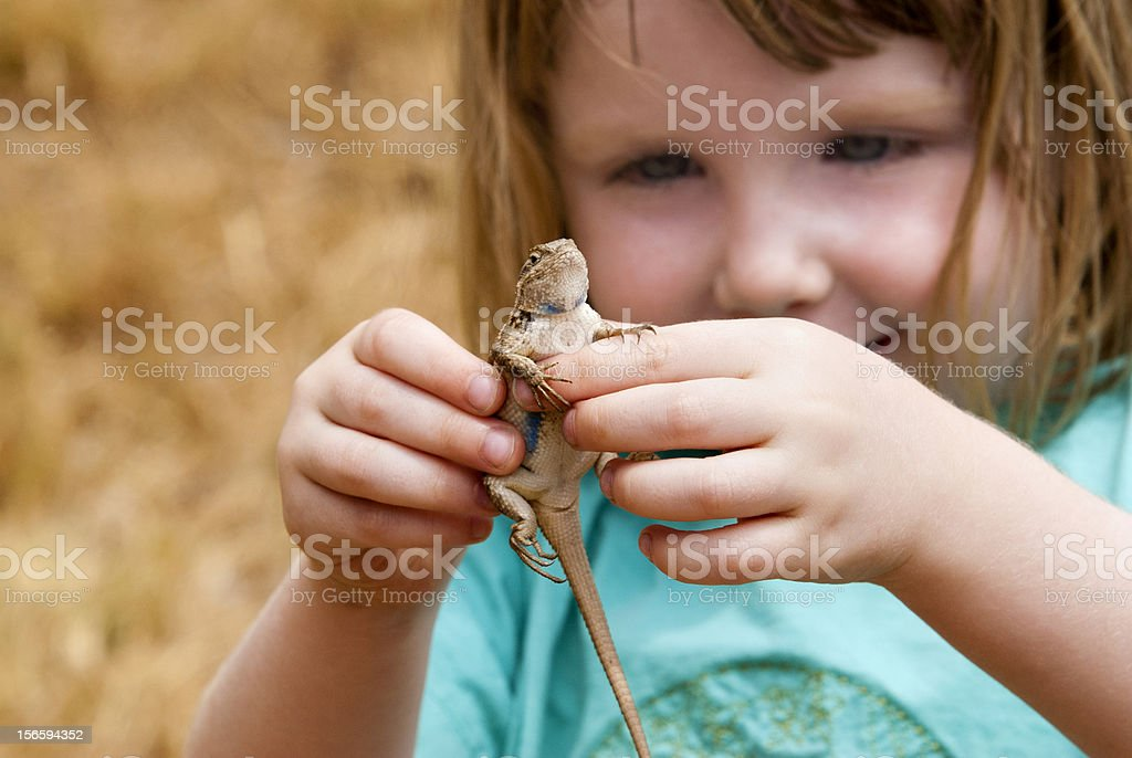 Happy Little Girl Holding A Lizard stock photo