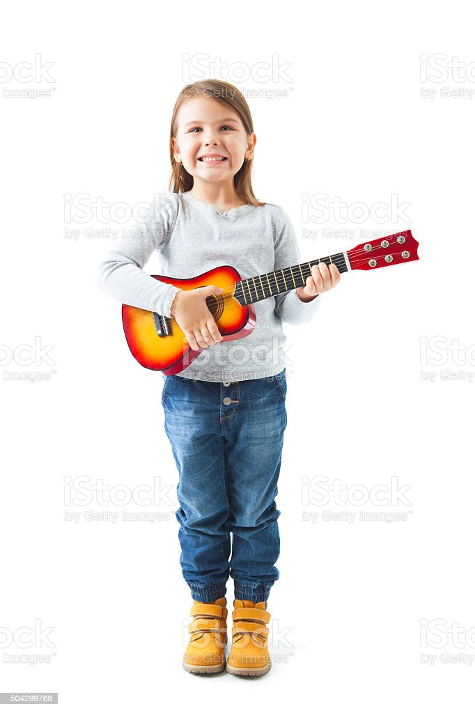 Happy little girl holding acoustic guitar stock photo