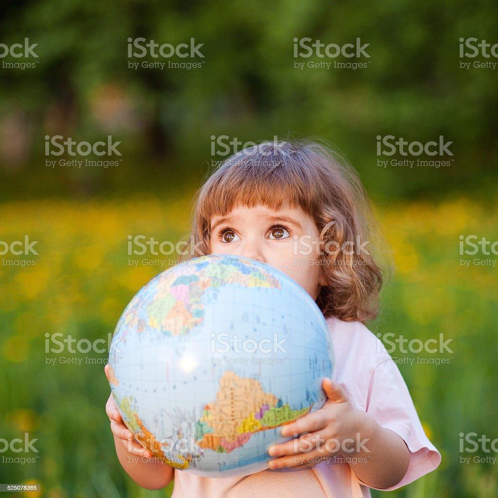 Happy little girl holding globe stock photo