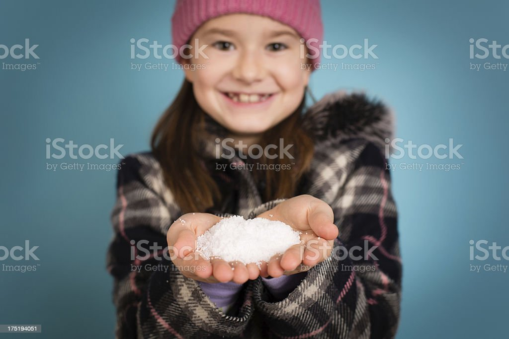 Happy Little Girl Holding Handful of Snow Towards Camera royalty-free stock photo