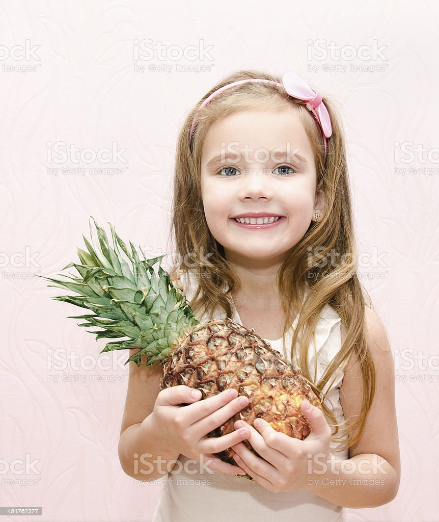 Happy little girl holding ripe whole pineapple royalty-free stock photo