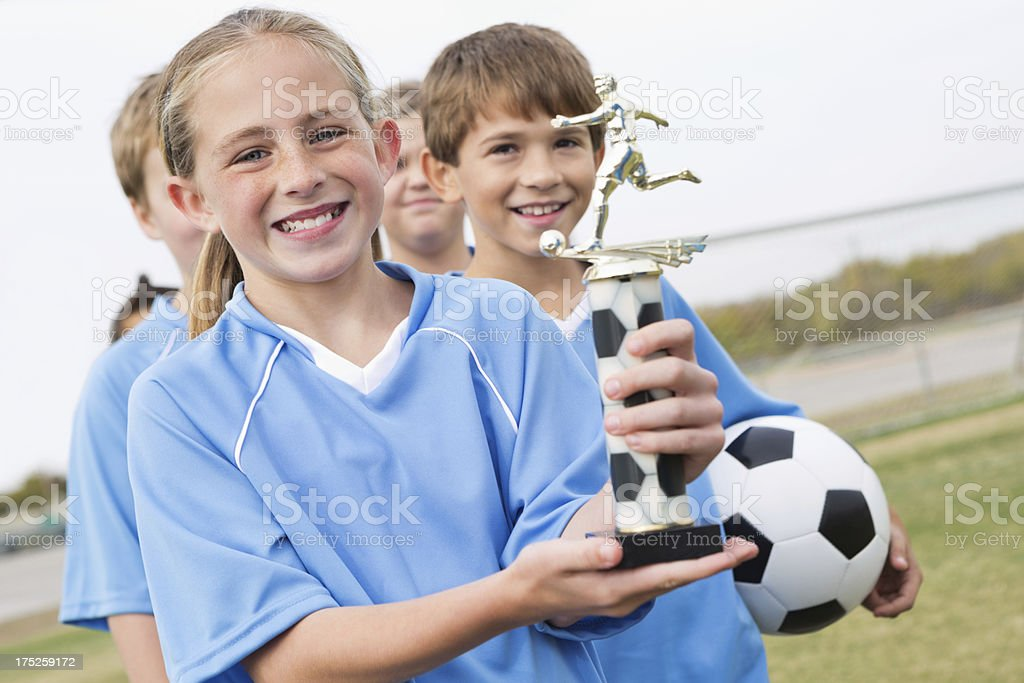 Happy little girl holding soccer trophy after winning game royalty-free stock photo