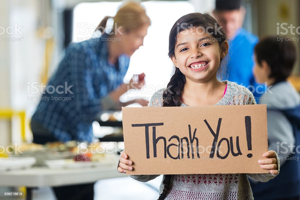 Happy little girl holding THANK YOU sign in food bank stock photo