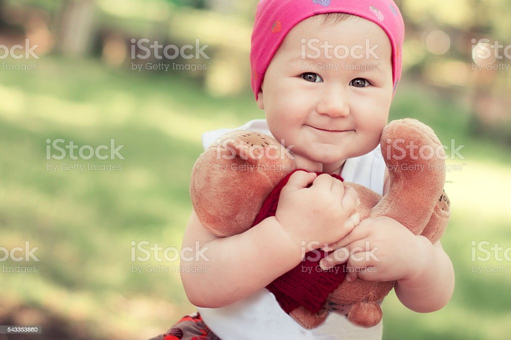 happy little girl in cap playing with Teddy bear stock photo