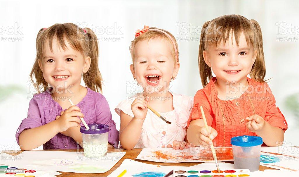 happy little girl in kindergarten draw paints stock photo