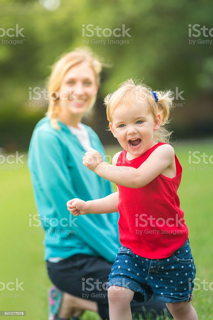 Happy little girl in patriotic colors running in field stock photo