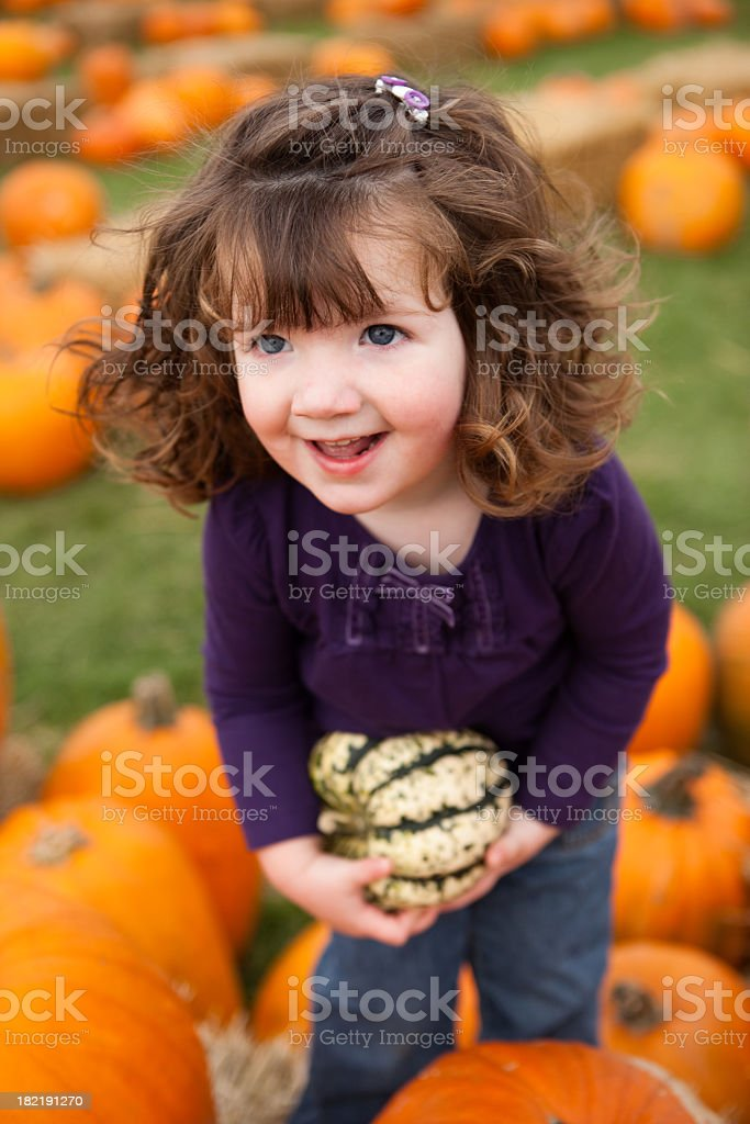 Happy Little Girl in Pumpkin Patch Holding a Gourd royalty-free stock photo