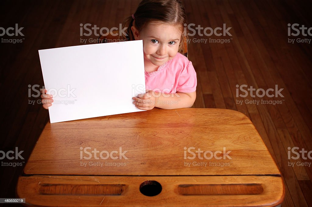 Happy Little Girl in School Desk Holding Blank Sign royalty-free stock photo