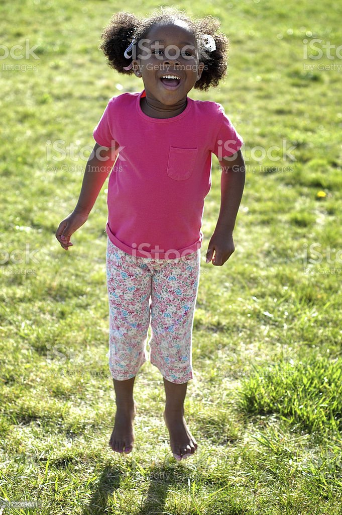 Happy Little Girl Jumping and Laughing Outside royalty-free stock photo