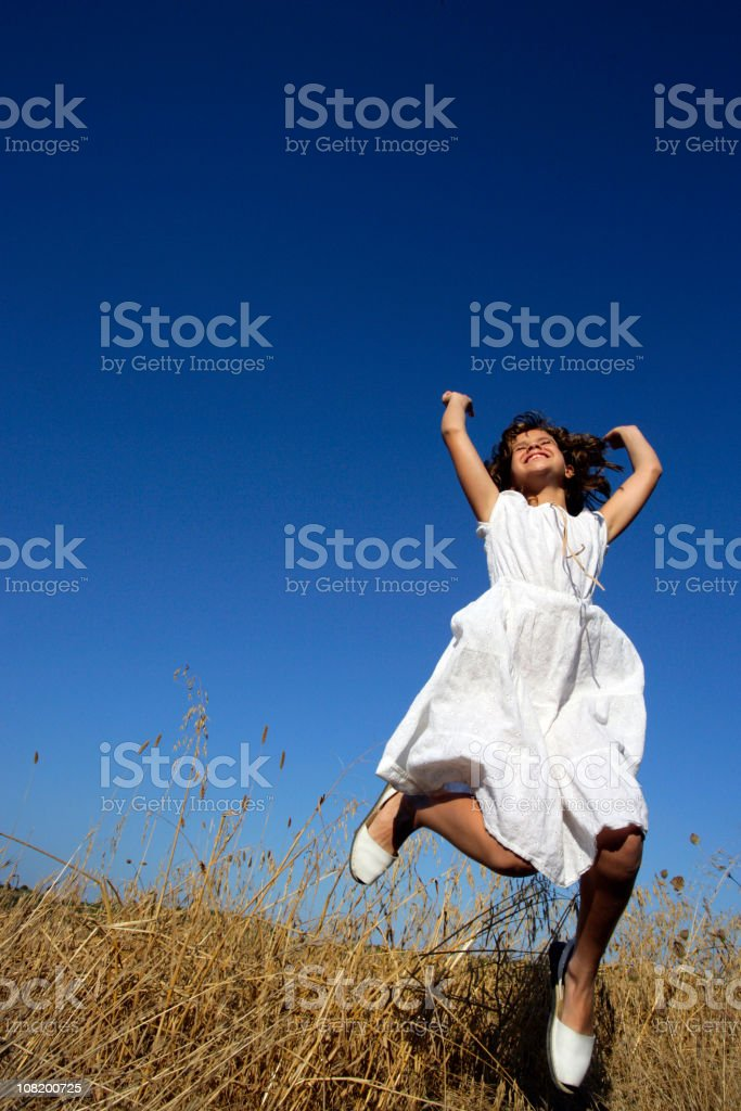 Happy Little Girl Jumping in Wheat Field royalty-free stock photo