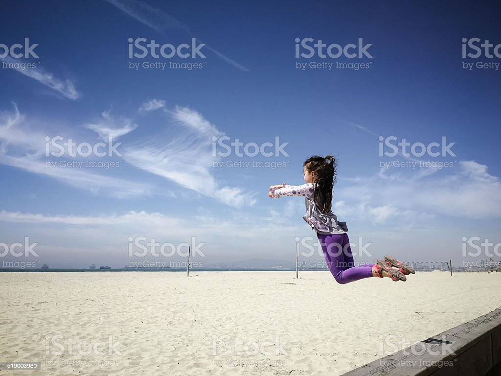 Happy little girl jumps in air at empty beach stock photo