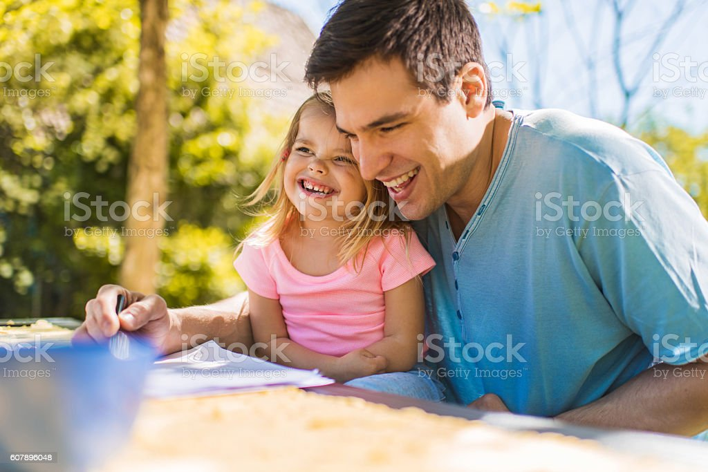Happy little girl laughing and having fun with her father. stock photo