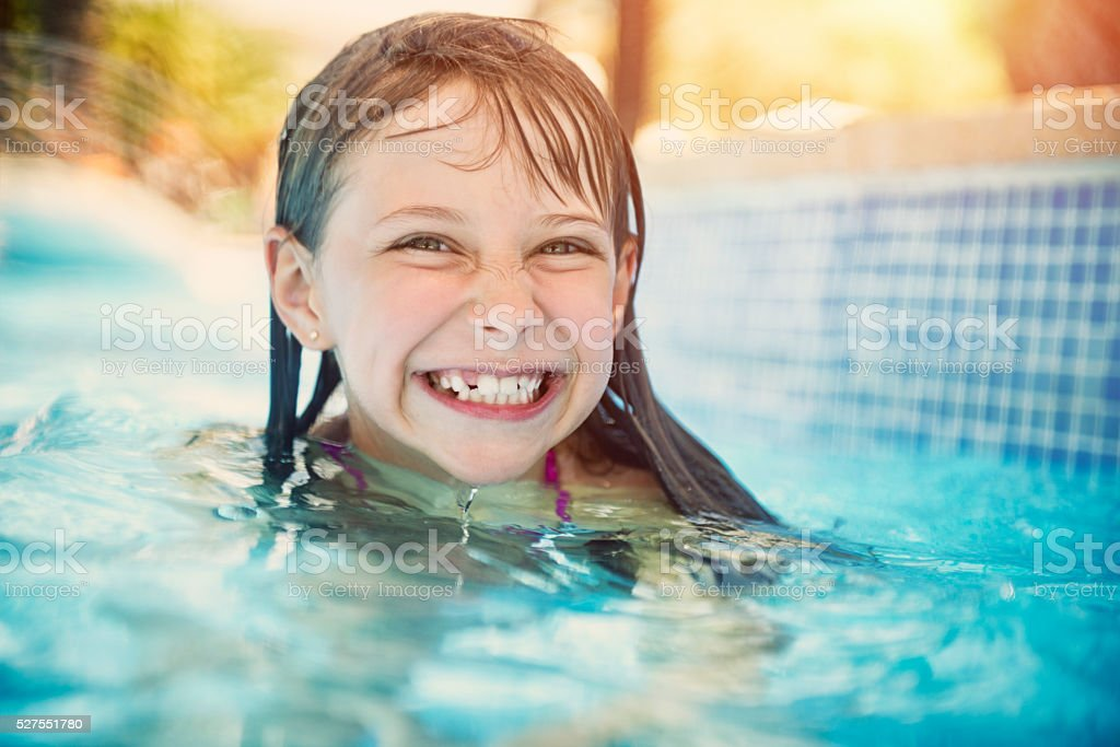 Happy little girl laughing in swimming pool stock photo