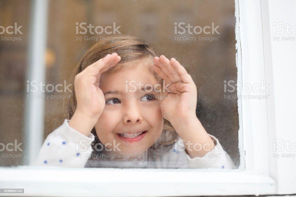 Happy little girl looking outside window stock photo