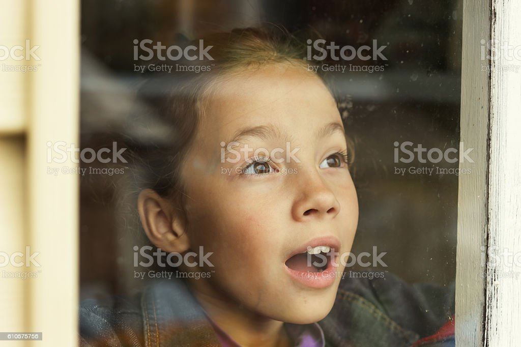Happy little girl looking through an old window stock photo