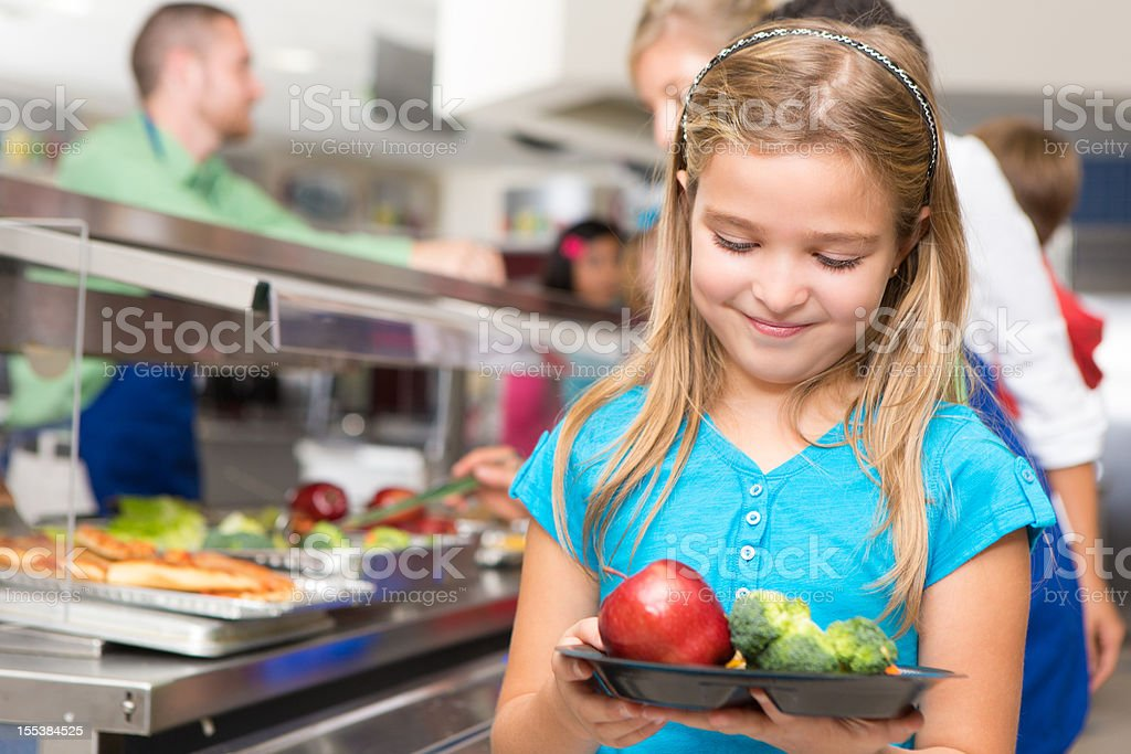 Happy little girl making healthy choices in school cafeteria royalty-free stock photo