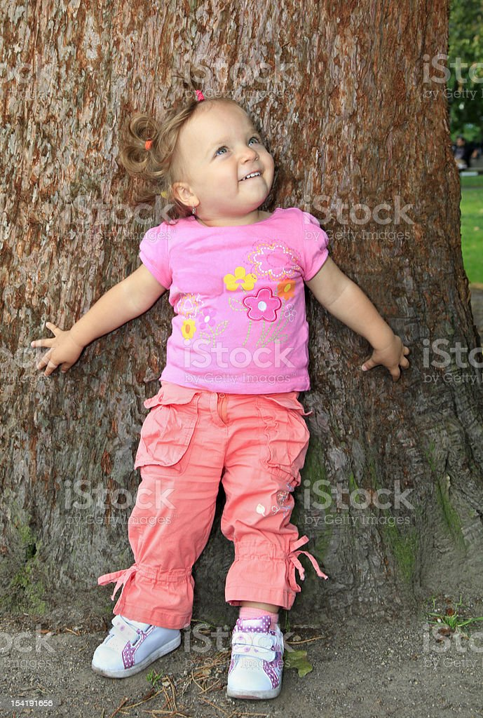 Happy little girl on a tree trunk background royalty-free stock photo