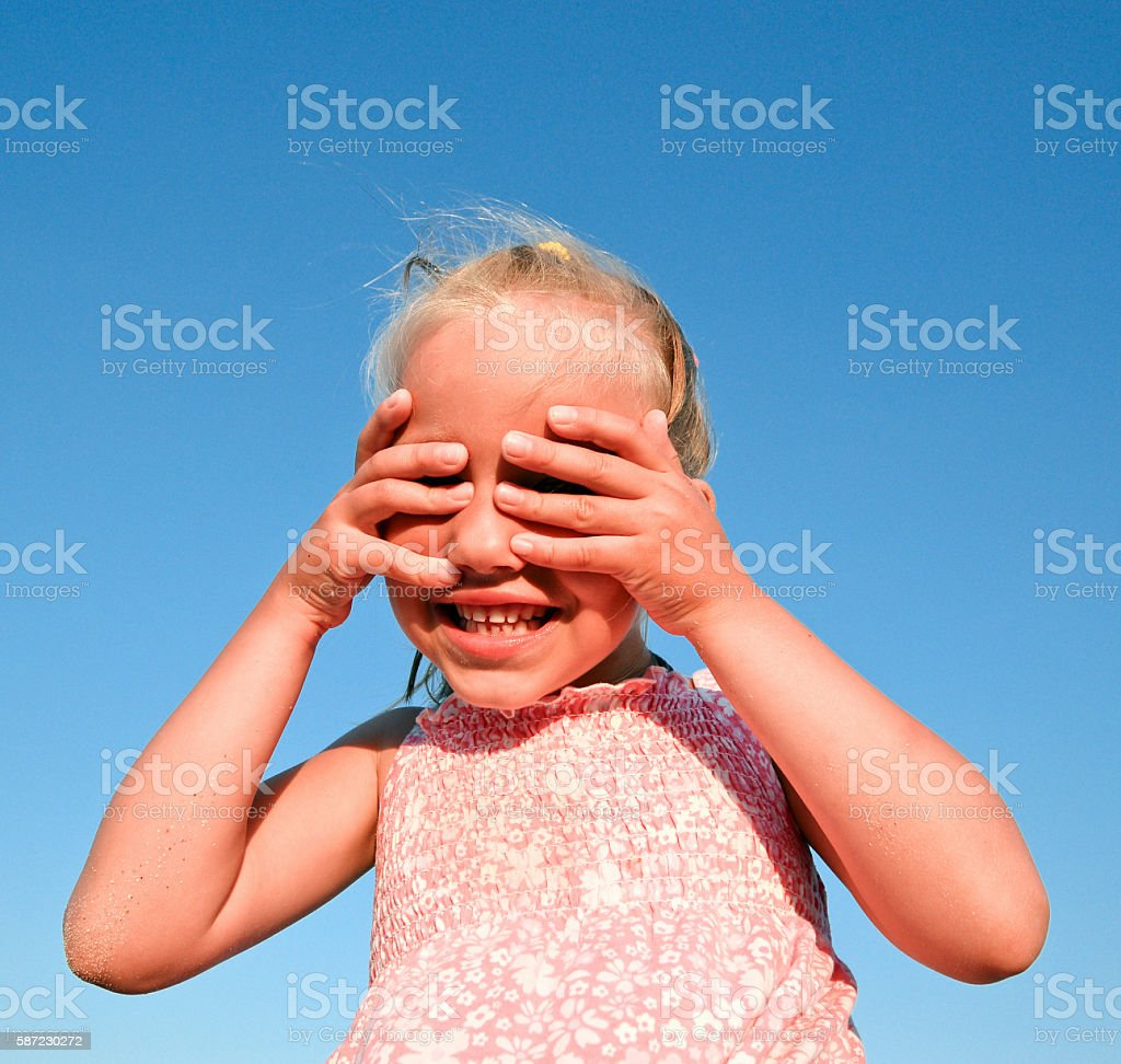 Happy little girl on bright blue sky background stock photo
