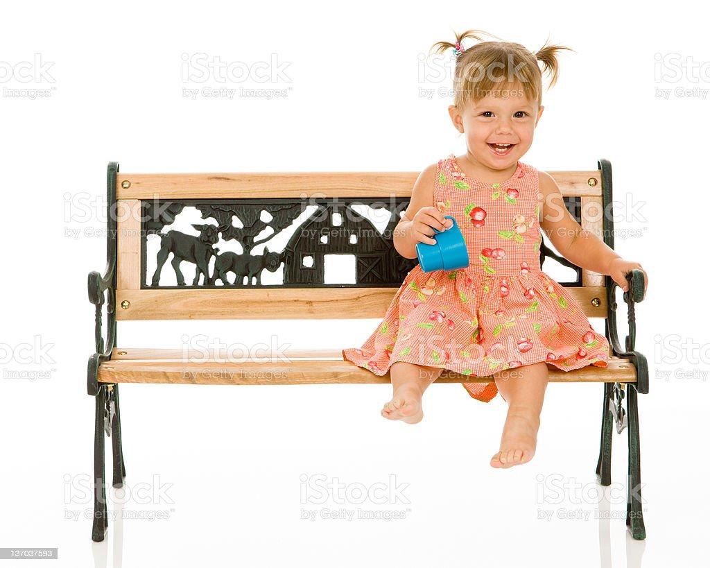 Happy Little Girl on Park Bench stock photo