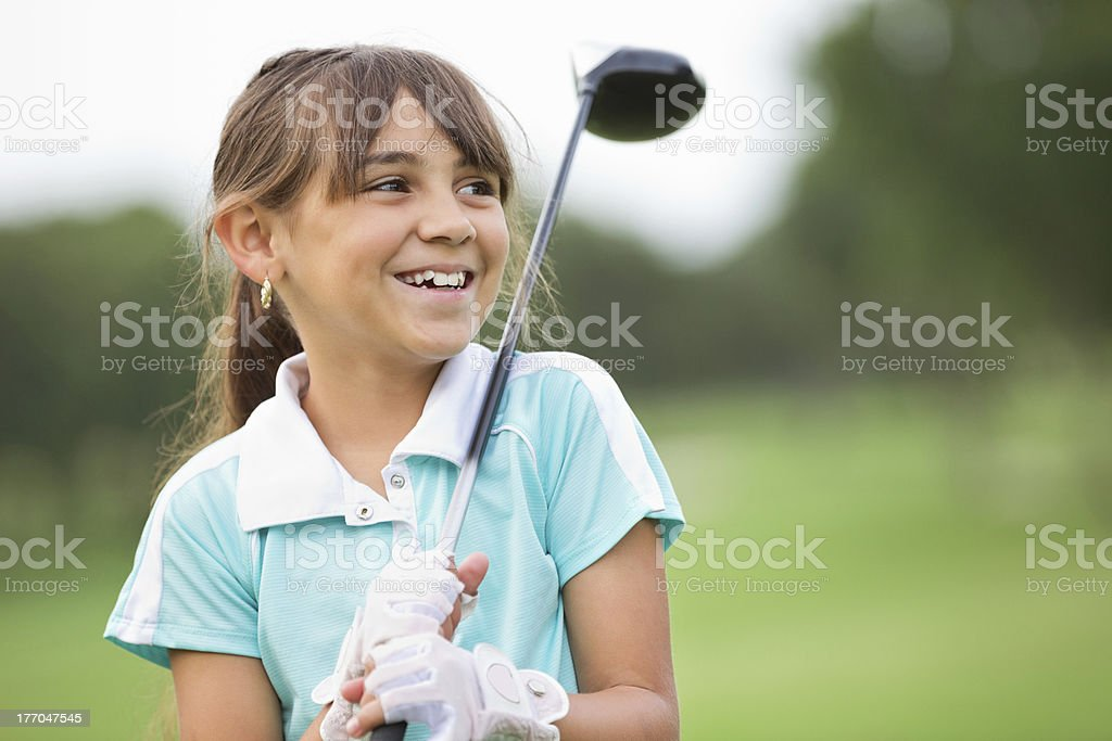 Happy little girl playing golf at country club stock photo