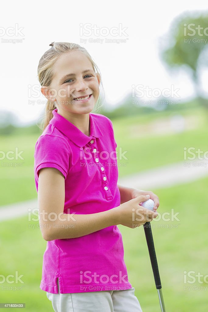 Happy little girl playing golf on course royalty-free stock photo