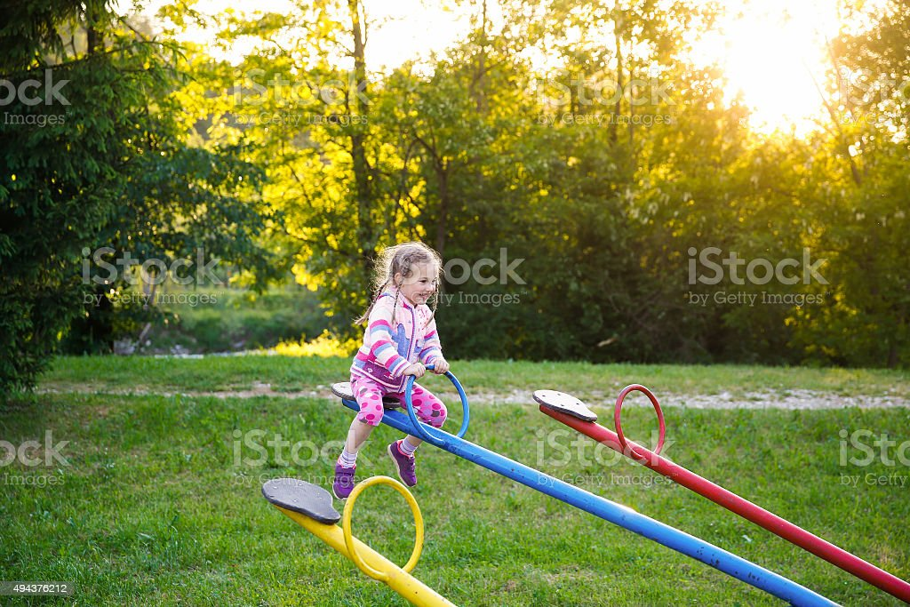 Happy little girl playing on a seesaw stock photo