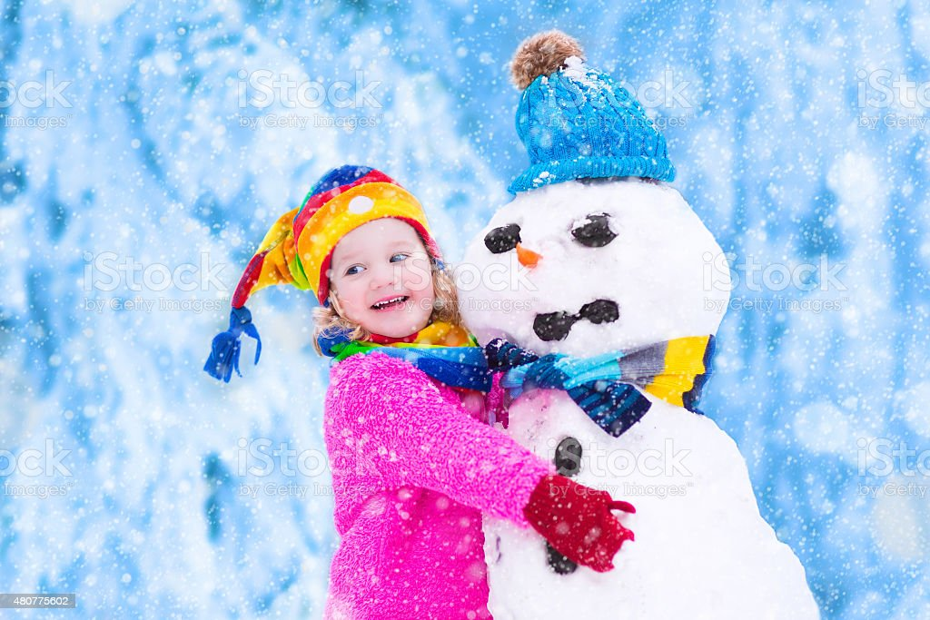 Happy little girl playing with a snowman stock photo