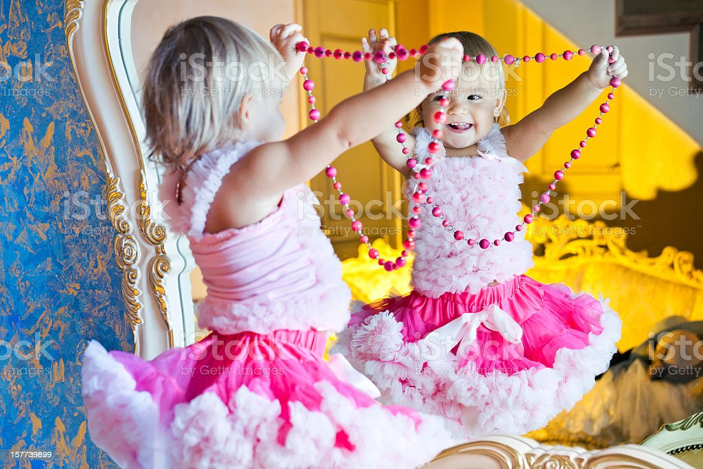 Happy little girl playing with beads stock photo