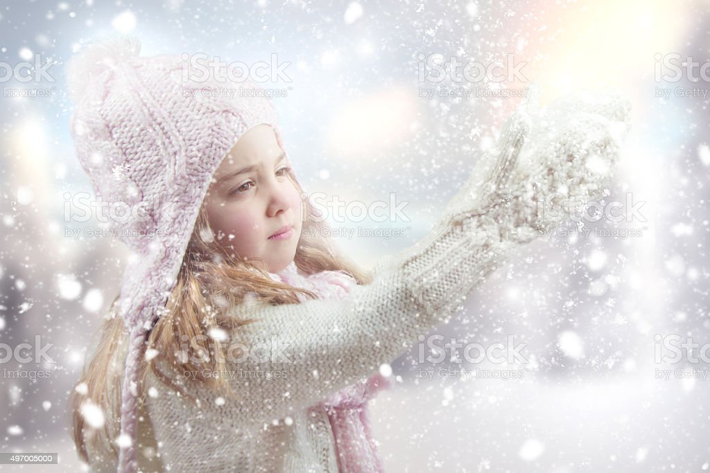 Happy little girl playing with snow. stock photo