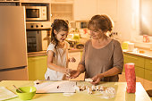 Happy little girl preparing sweet food with her grandmother.