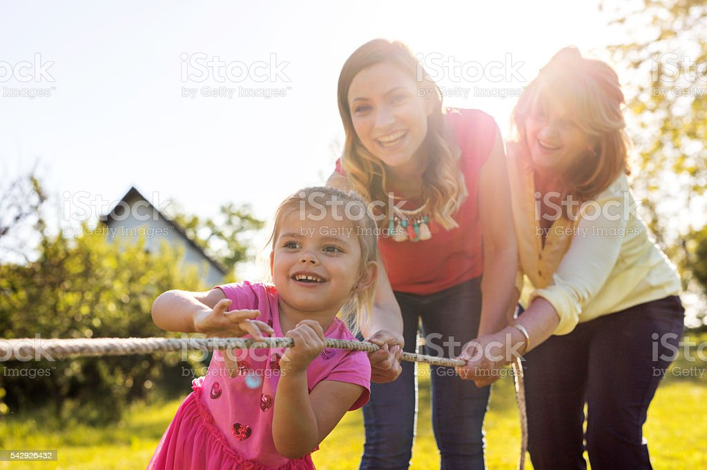 Happy little girl pulling rope with her mother and grandmother. stock photo