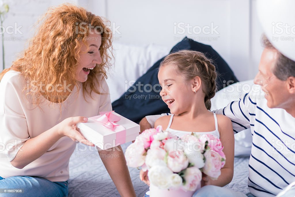 Happy little girl receiving a present from her grandparents stock photo
