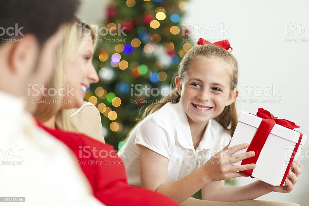 Happy little girl receiving Christmas present from parents royalty-free stock photo