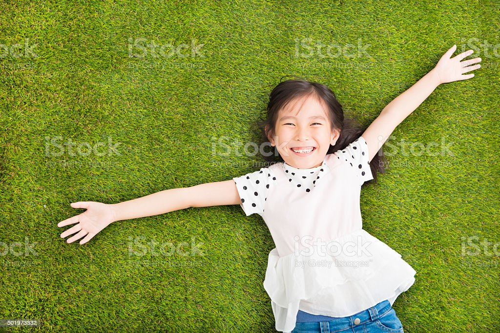 happy Little  girl resting on the grass stock photo