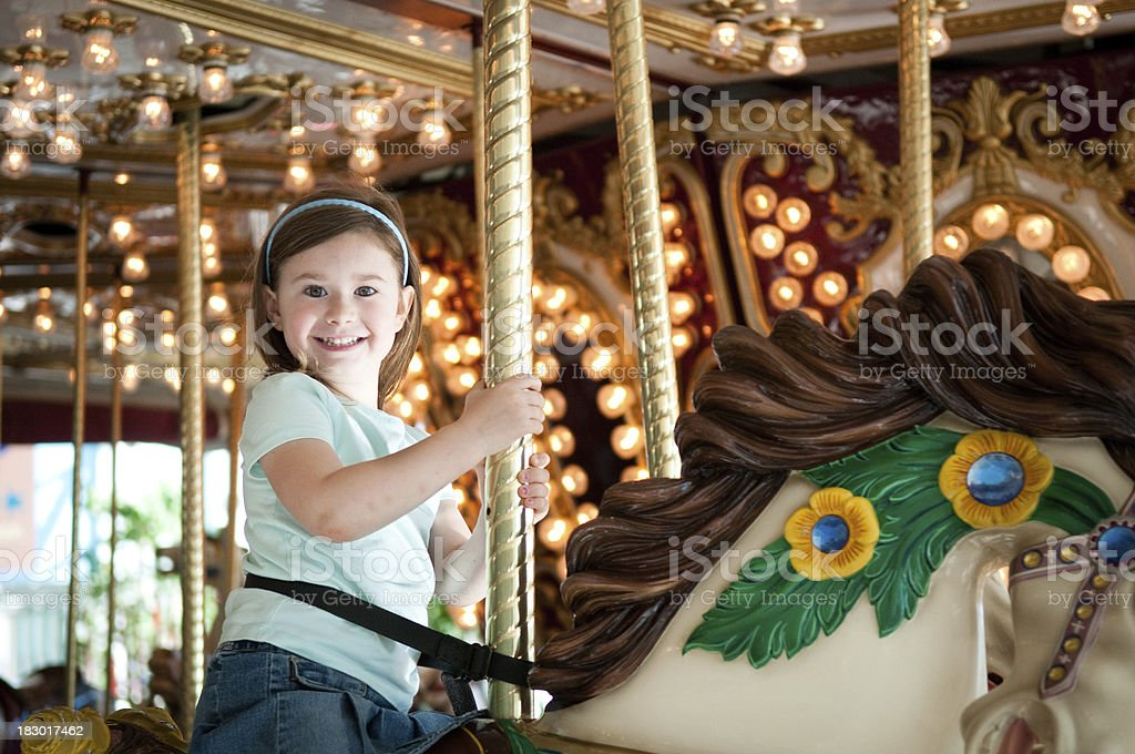 Happy Little Girl Riding Carousel Horse stock photo