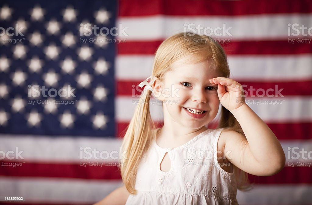 Happy Little Girl Saluting with American Flag royalty-free stock photo