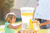 Happy little girl sells lemonade in front yard