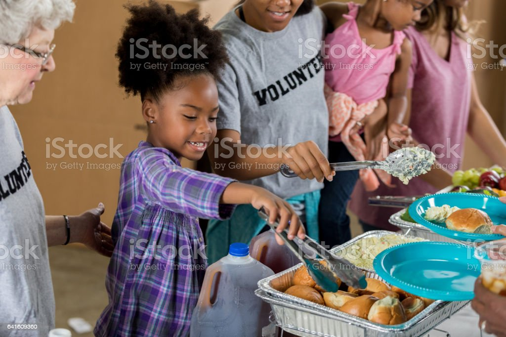 Happy little girl serves meal in soup kitchen stock photo