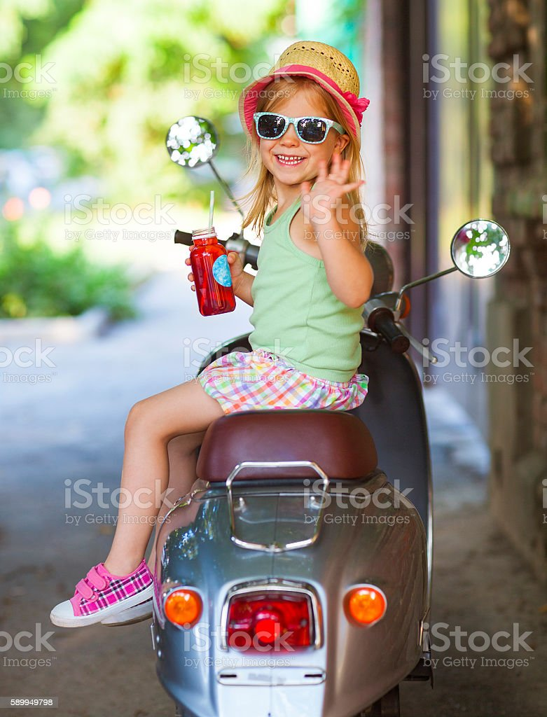 Happy little girl sitting on vintage scooter in the street stock photo
