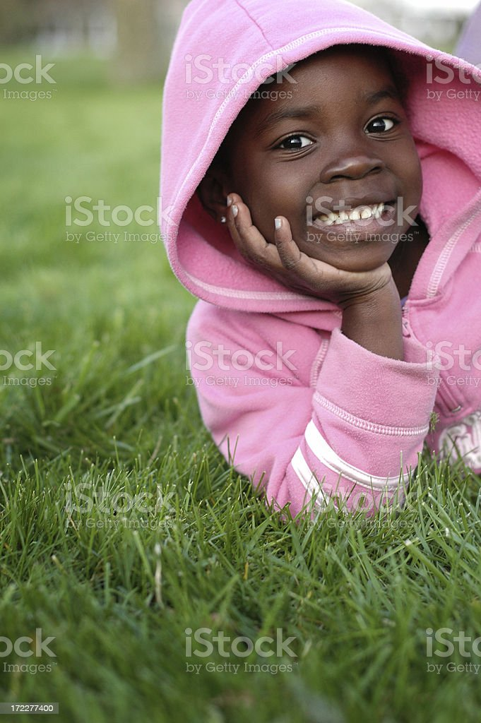 Happy Little Girl Smiling in the Grass Outside royalty-free stock photo