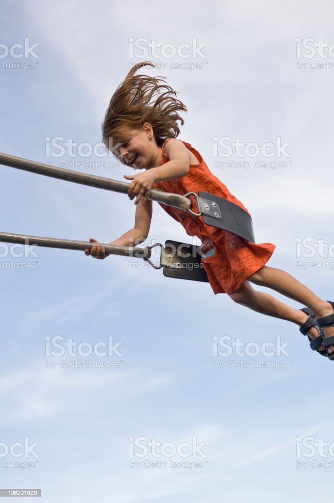 Happy Little Girl Swinging on Swing stock photo