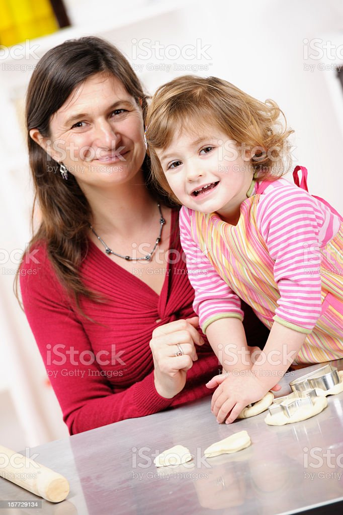 Happy Little Girl/ Toddler Preparing Dough With Her Mother stock photo
