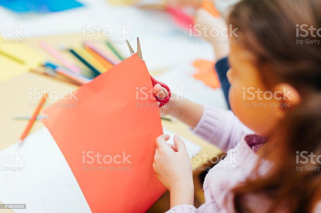 Happy Little Girl using scissors in kindergarten. stock photo