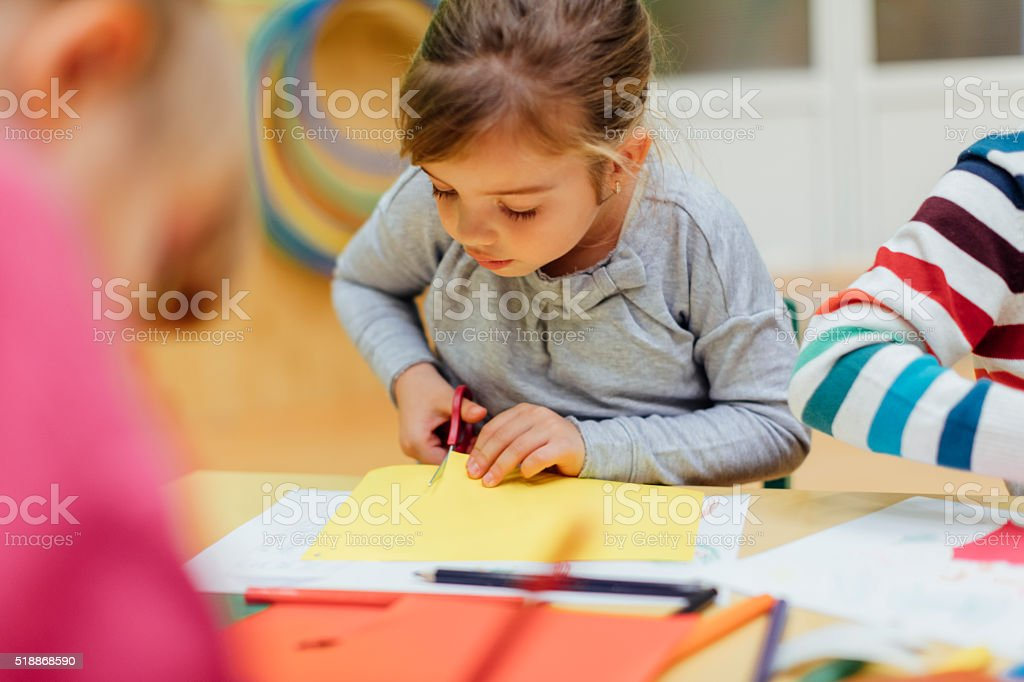 Happy Little Girl using scissors in kindergarten. stock photo