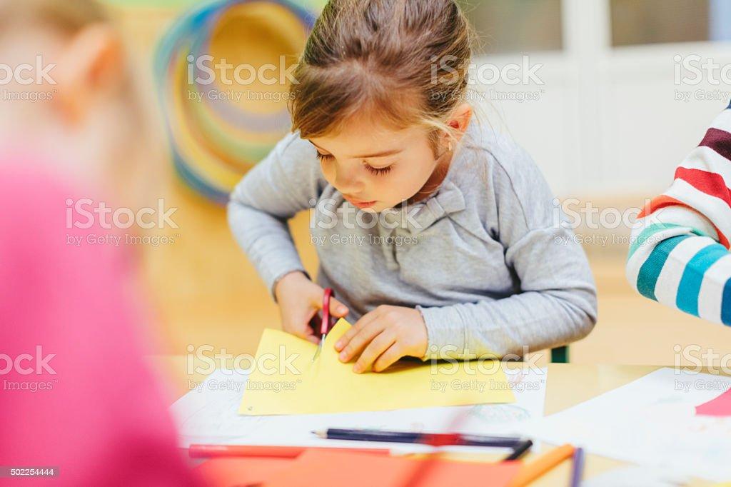 Happy Little Girl Using Scissors. stock photo