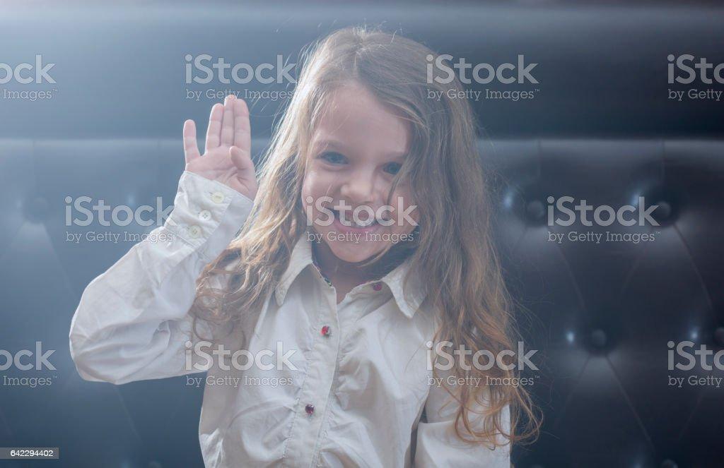 Happy little girl waving at camera stock photo