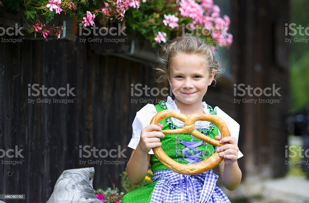 Happy little girl wearing a traditional Bavarian dress dirndl stock photo