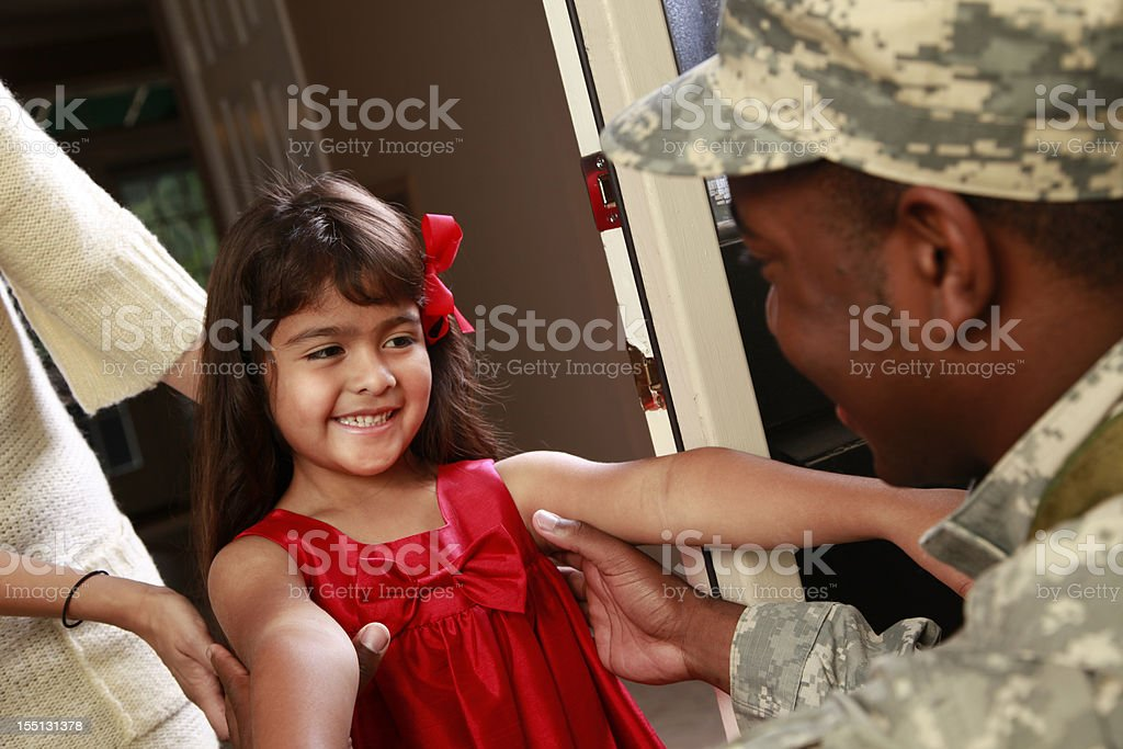 Happy little girl welcoming home military soldier father. stock photo