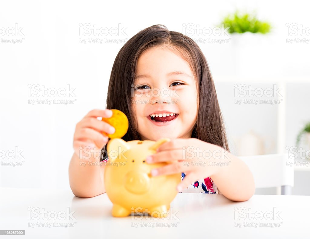 happy little girl with a piggy bank stock photo